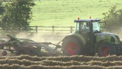 Stock Video Footage of Tractor tows hayrake across field.