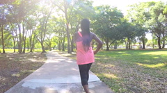 Young active African American woman power walking in park to keep healthy - stock footage