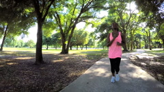 Young active African American fitness female enjoying jogging in park - stock footage