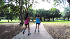Young active multi ethnic American girls enjoying rollerblading outdoor - stock footage