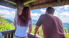 Stock Video Footage of A young and energetic couple observing the view from the lookout tower