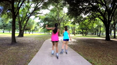 Young slim multi ethnic females inline skating in park - stock footage