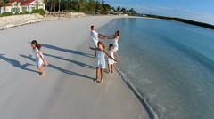 Aerial drone of young Caucasian family on sandy beach - stock footage