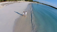 Aerial drone loving young Caucasian couple walking Caribbean beach - stock footage