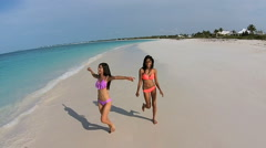 Aerial view multi ethnic girlfriends in swimwear on tropical beach - stock footage