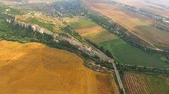 Aerial View Of Yellow Harvest Field And Hilly Terrain Stock Footage