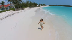 Aerial drone young ethnic girl wearing sundress sunhat barefoot on beach - stock footage