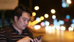 Asian tourist Man using on mobile phone at night in city. - stock footage