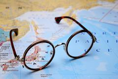 Glasses on a map of Asia - Tokyo - stock photo