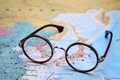 Glasses on a map of Asia - Tokyo Stock Photos
