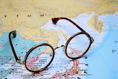 Glasses on a map of Asia - Pyongyang - stock photo