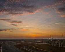 Passenger plane fly up over take-off runway from airport at sunset Kuvituskuvat