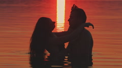 Girl and boy swimming at sunset Stock Footage