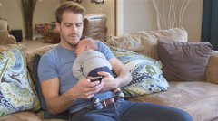 Father texting with newborn son asleep on his chest - stock footage