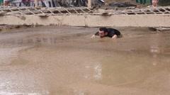 Man crawling in a mud bath Stock Footage