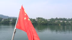 Chinese national flag flying from a boat sailing in the lake Stock Footage