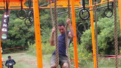Man trying to pull himself across on rings and ropes Stock Footage