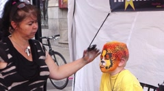 Doing face painting on a young boy - stock footage