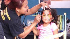 Woman painting the face of a young Asian girl - stock footage
