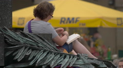 Reading a book at the Adam Mickiewicz Monument, Krakow Stock Footage