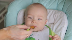 Mother feeding little baby with a spoon Stock Footage