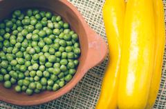 ceramic terracota bowl of fresh organic green peas next to exquisite yellow - stock photo