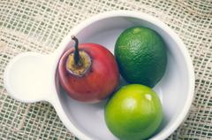Aromatic garden-fresh tree tomato and limes in white bowl Stock Photos