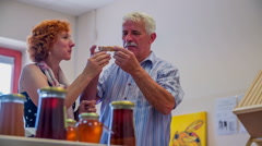 Am older man eating bread with honey in a store where honey is produced Stock Footage