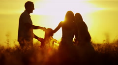 Carefree Caucasian Family Enjoying Vacation Together Outdoors Sunrise Silhouette - stock footage