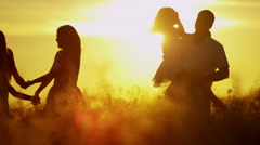 Carefree Caucasian Family Enjoying Vacation Together Outdoors Sunset Silhouette - stock footage