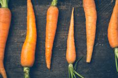 All-natural carrots lined up on wooden board rustic concept Stock Photos