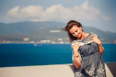 Brunette girl in short grey frock smiles by wall against sea Stock Photos
