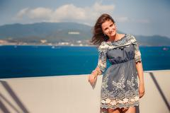brunette girl in short grey frock smiles by wall against sea - stock photo