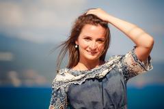 brunette girl in grey frock smiles against defocused sea - stock photo