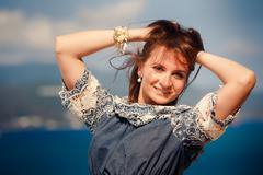 Brunette girl in grey frock smiles against defocused sea Stock Photos