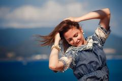 brunette girl in grey frock smoothes hair against sea - stock photo