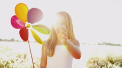 Young Caucasian Girl Playing Outdoors Toy Windmill Clean Environmental Energy - stock footage