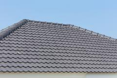 black roof tiles on house with blue sky - stock photo