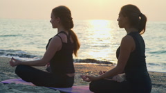 Two young females practice yoga on the beach slow motion Stock Footage