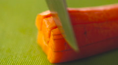 Carrots cut with a knife close up slow motion Stock Footage