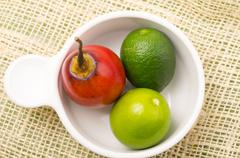 Aromatic garden-fresh tree tomato and limes in white bowl Stock Photos