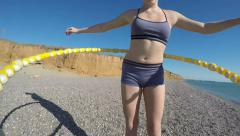Young girl having fun twirling fitness hula hoop on the beach Stock Footage
