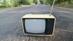 Old fashioned Tv with flickering screen on empty countryside road Stock Footage