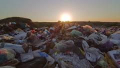 Sun setting over landfill site of domestic waste jib shot Stock Footage