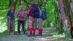 Four senior hikers are talking in the nature and showing something to each other Stock Footage