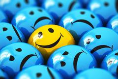 Single happy yellow smiley among blue sad ones - stock illustration