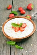 Oatmeal porridge with strawberry slices - stock photo