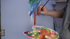 Girl with a brush paints a parrot on the canvas. - stock footage