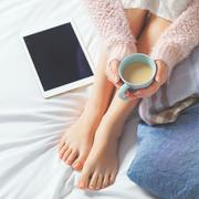 Woman using tablet at cozy home atmosphere on the bed. Young beautiful woman  Stock Photos