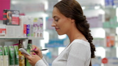 Beautiful girl customer making notes in drugstore Stock Footage